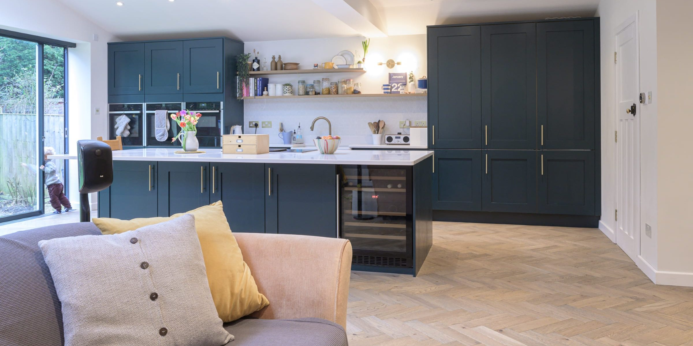 blue kitchen with herringbone wood floors