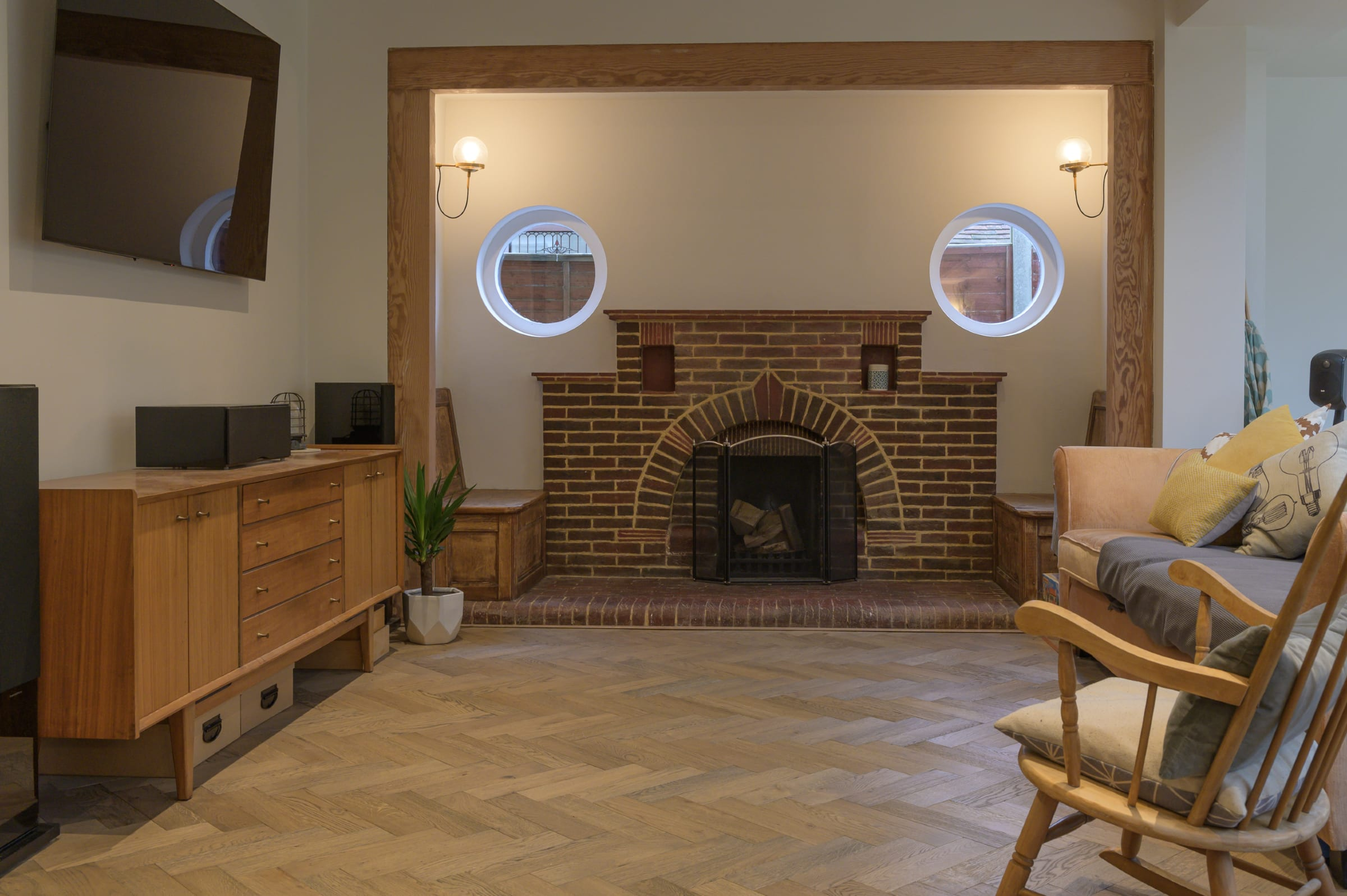 brick fireplace and herringbone wood floors